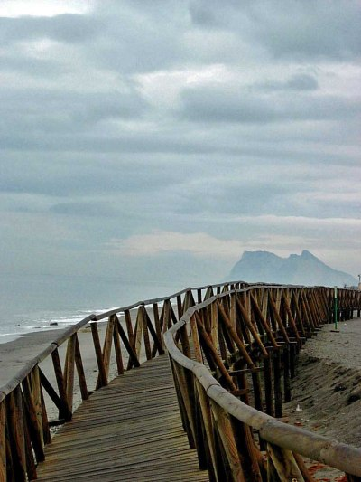 The boardwalk that used to be in place along the beach with Gibraltar in the background